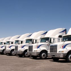 Semi truck fleet lined up in a row with copy space